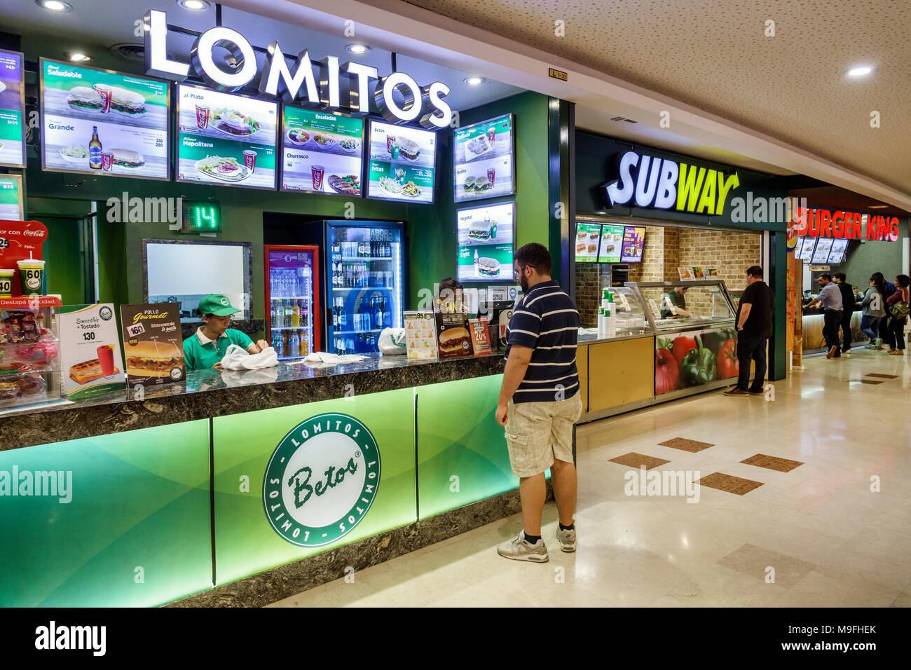 Buenos Aires Argentina Galerias Pacifico food court plaza interior Lomitos steak sandwich shop counter man woman Hispanic Argentinean Argentinian Argentine South America American - Stock Image