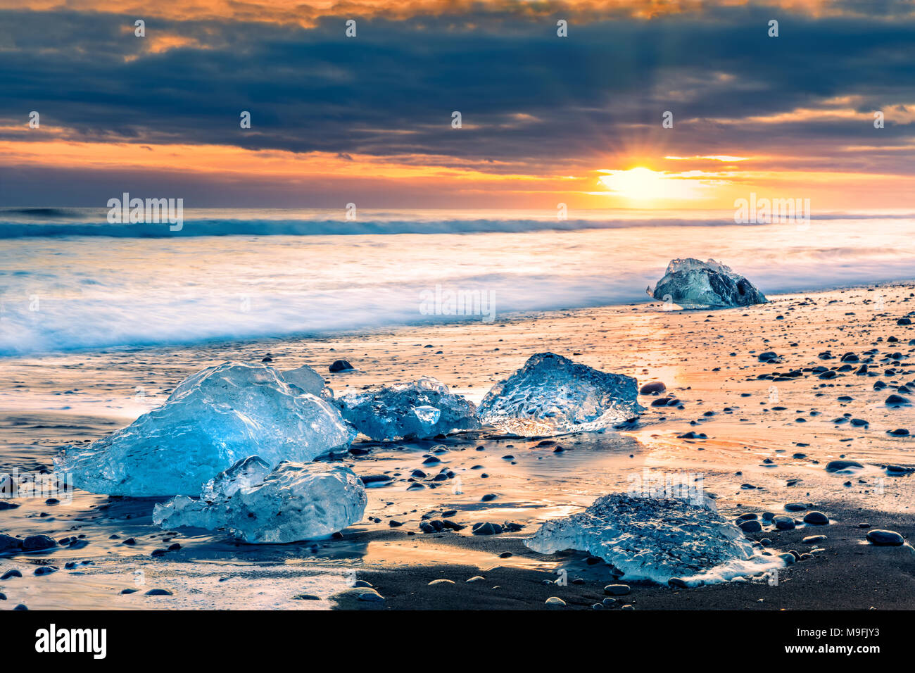 Drifting ice blocks on Diamond beach, at sunset, in Jokulsarlon, Iceland - Stock Image