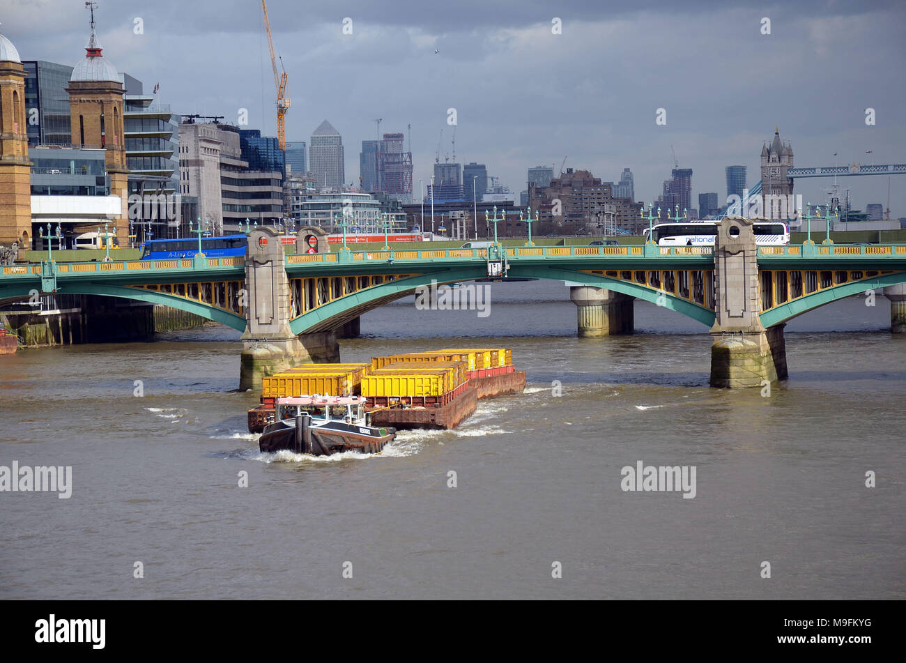 London, UK, 23 March 2018 Tug pulling barge with rubbish containers on the River Thames. Rubbish is taken to landfill in Essex. - Stock Image