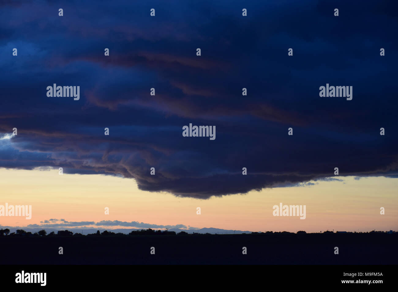 Dark clouds in a stormy sky at dusk - Stock Image