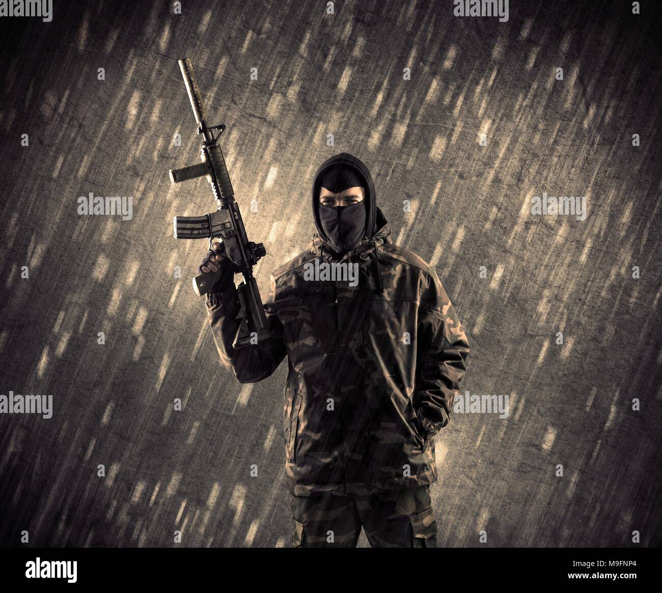 Close up of an armed terrorist man with mask on rainy background - Stock Image