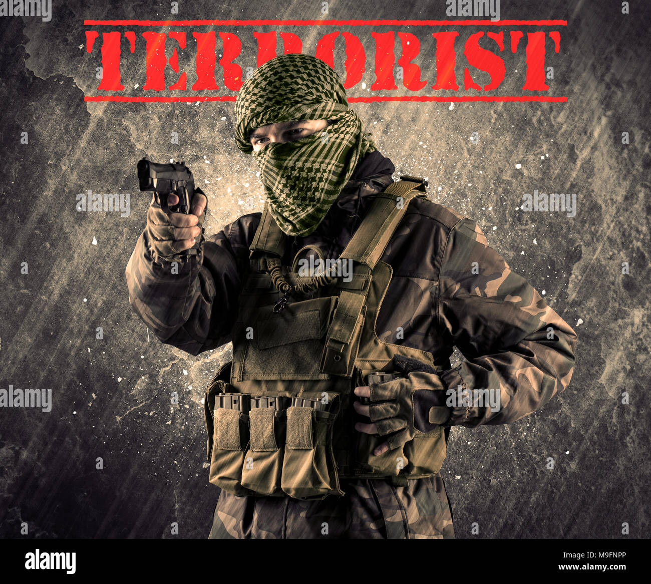Portrait of dangerous masked and armed man with terrorist sign on grungy background - Stock Image