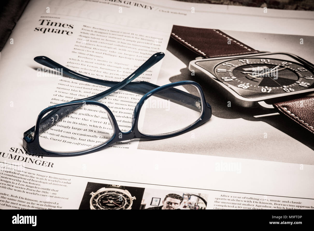 Reading glasses placed on financial newspaper - Stock Image