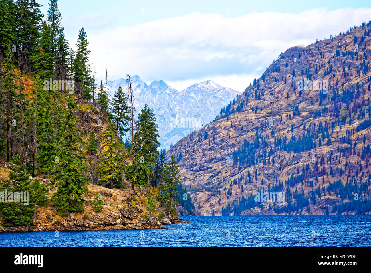 41,926.03489 dry mountains & conifer forests at Lake Chelan, with its deep canyon & scattered fall color, old forest fire hillside in the distance - Stock Image