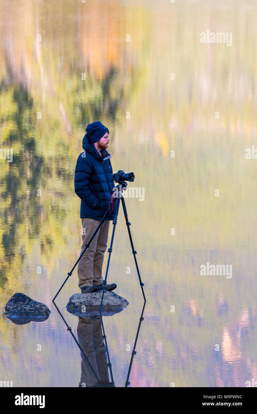 42,641.06237 Cold landscape photographer in warm jacket patiently standing on rock in a calm mirror like lake, waiting for perfect moment, reflections - Stock Image