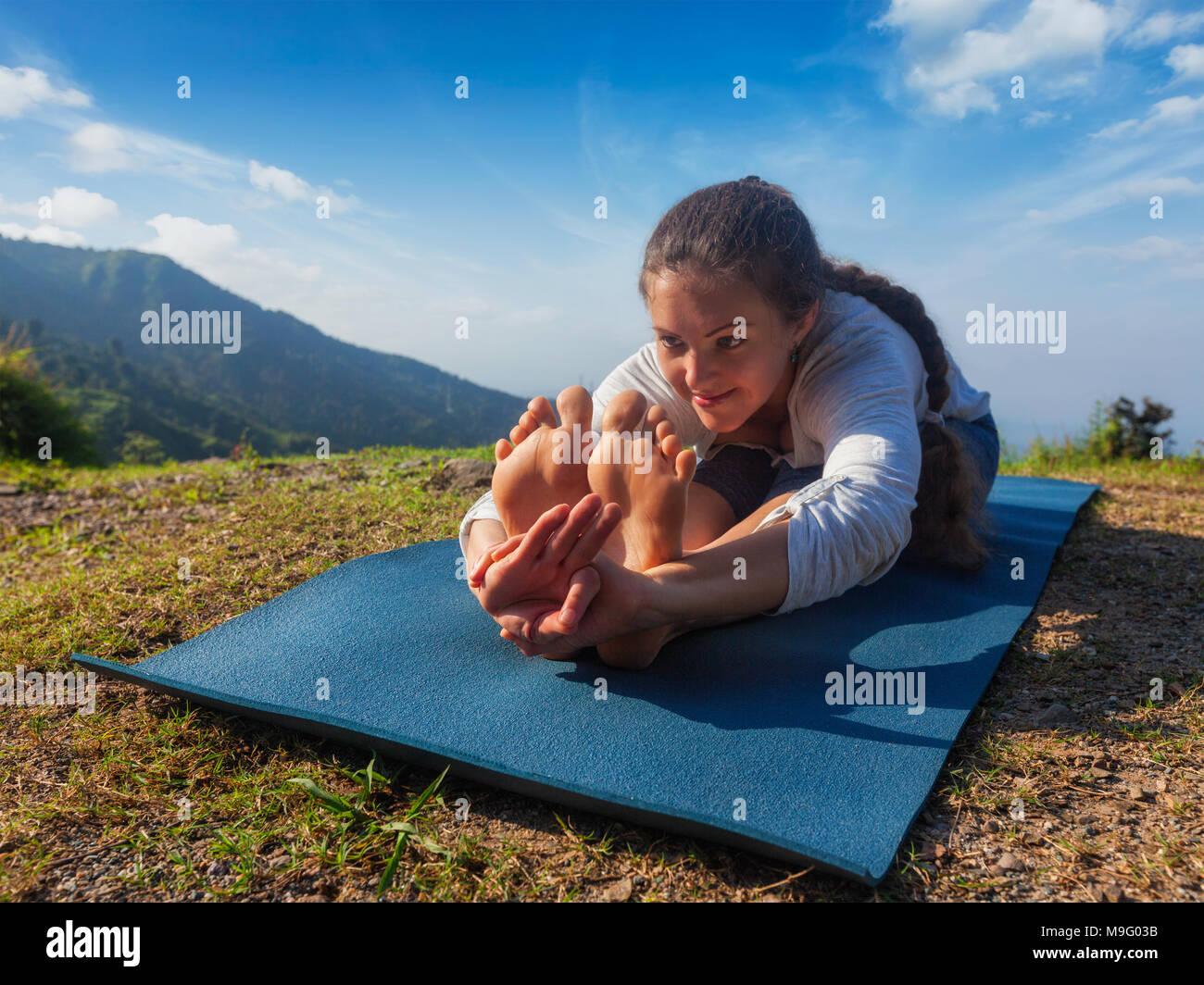 Woman doing yoga asana Paschimottanasana forward bend - Stock Image