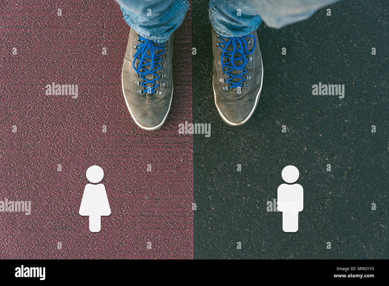 Gender gap between man and woman in past, now and future symbolized by two feet standing on two different colors with arrows on pathway from above - Stock Image