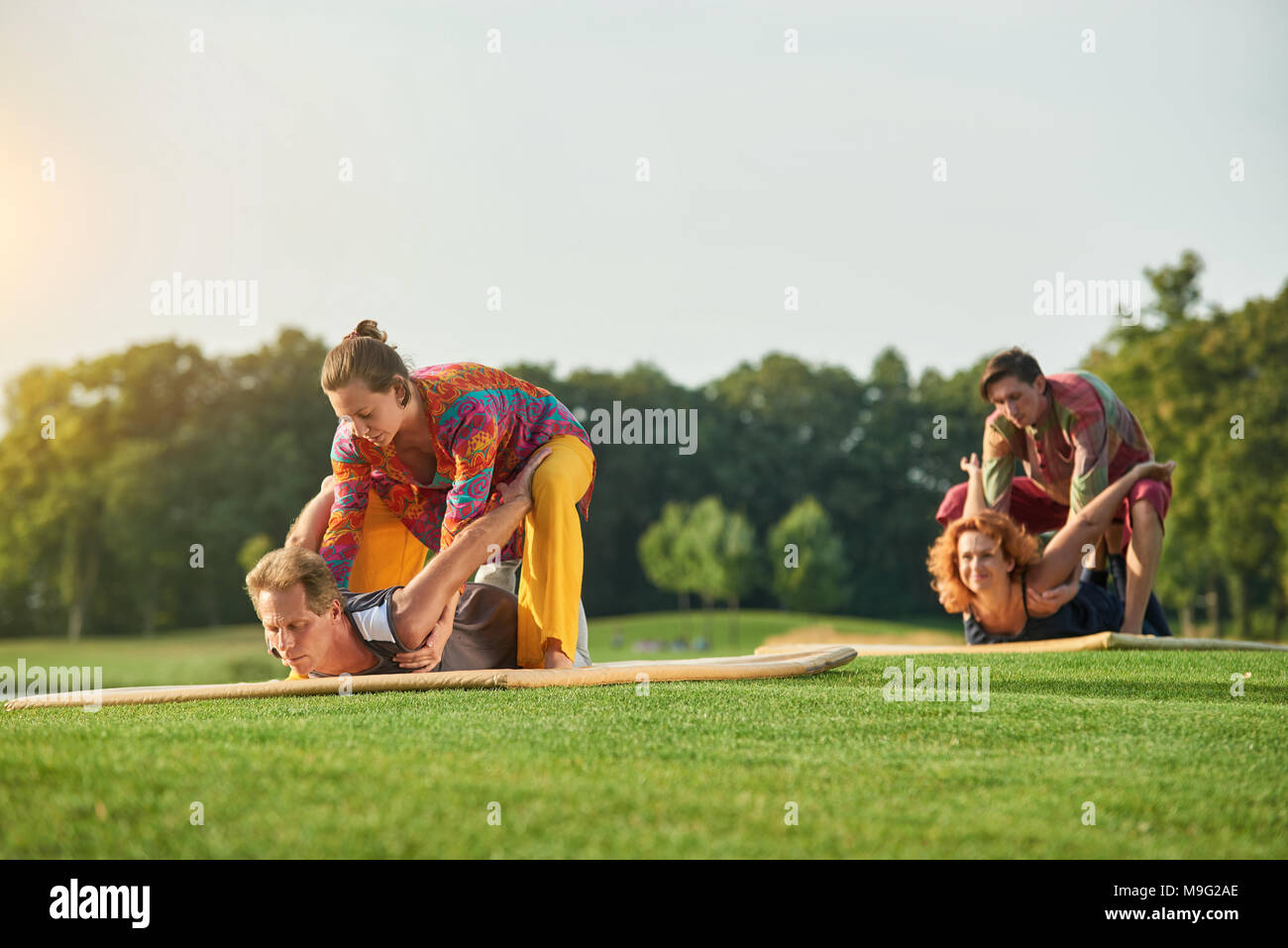 Yoga pose lying on stomach. Group thai massage on the lawn Stock