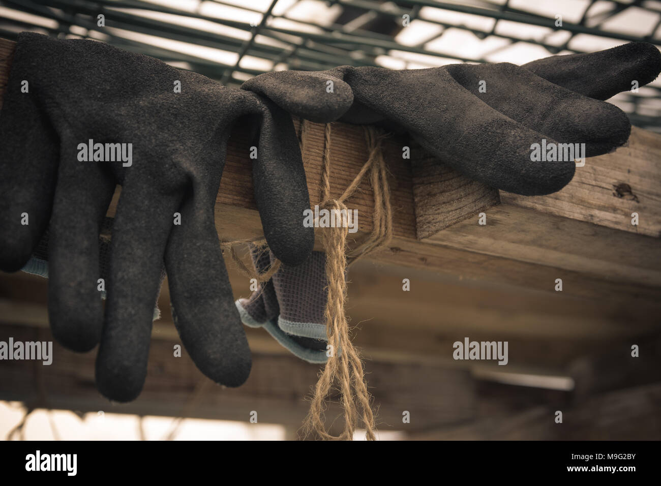 Close up of rubber gloves of a farmer lying in greenhouse. Hard work concept. Vintage style. - Stock Image