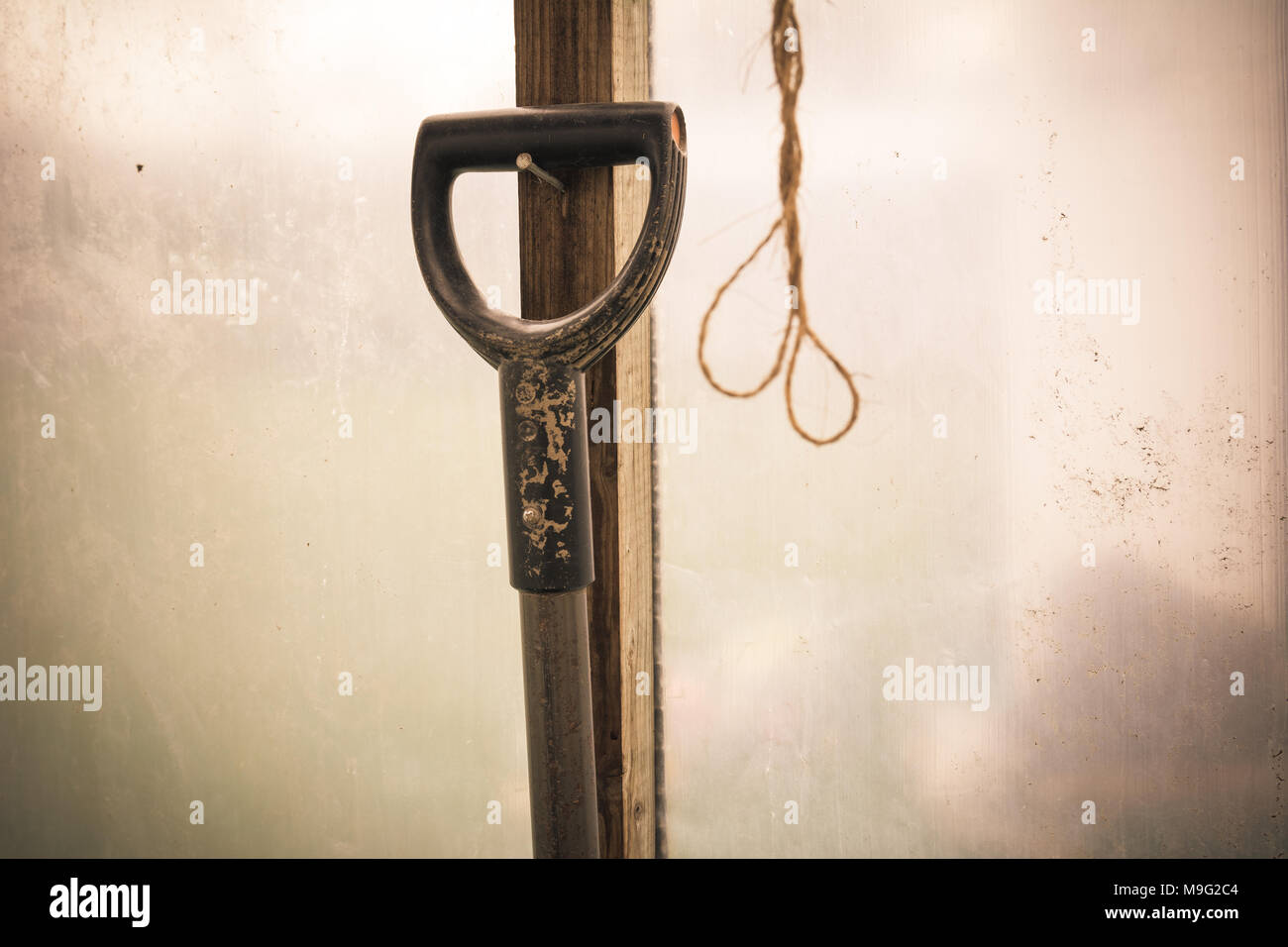 Shovel hanging on a nail in old greenhouse. Farmer work concept. Vintage style. - Stock Image