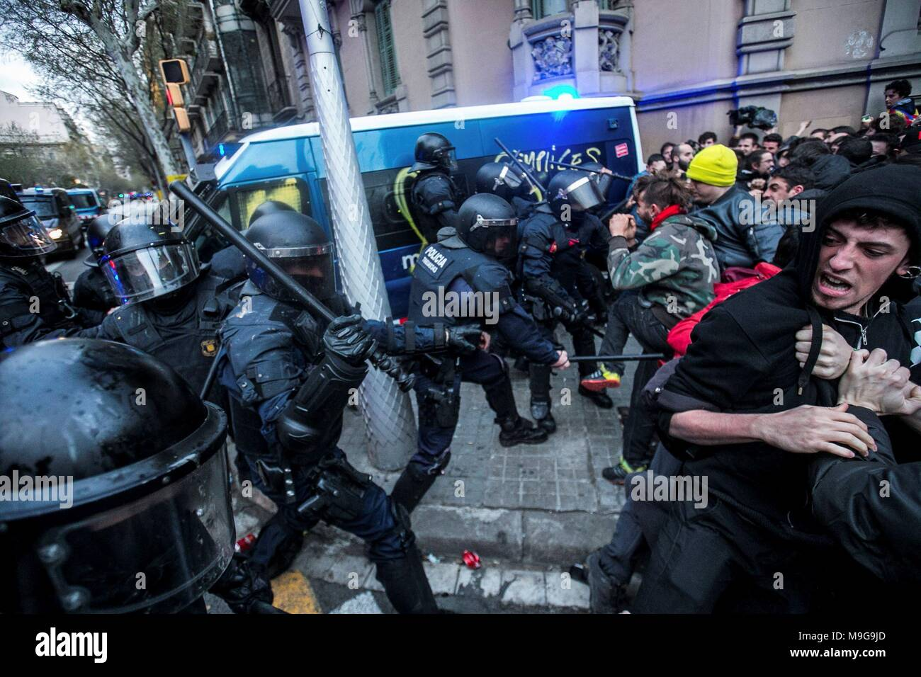 Catalonian riot police members and protesters clash during a protest against the detention of former Catalan leader Carles Puigdemont at the Spanish Government Delegation in the Autonomous Community of Catalonia in Barcelona, Catalonia, north eastern Spain, 25 March 2018. According to reports, German police on 25 March 2018 allegedly detained former Catalan leader Puigdemont after he crossed into Germany from Denmark. Puigdemont is sought by Spain who issued an European arrest warrant against the former leader who was living in exile in Belgium. EFE/ Enric Fontcuberta Stock Photo