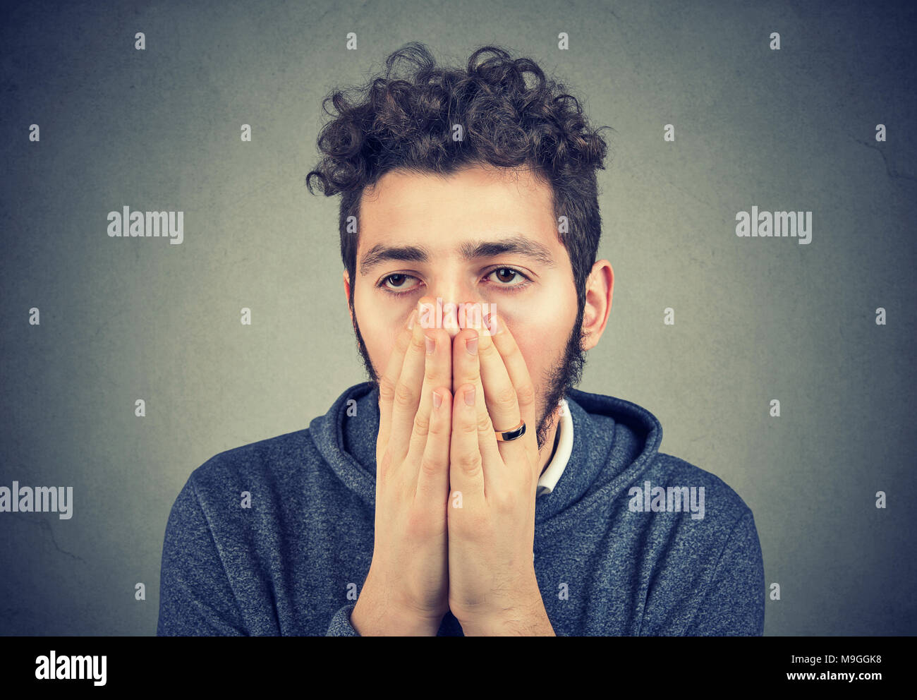Hipster guy having big problem and covering face dramatically looking away. - Stock Image