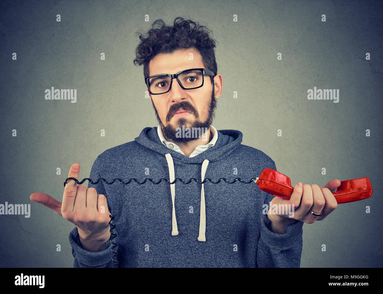 Disgusted young man looking at camera with bewilderment and confusion holding old fashioned red handset. - Stock Image