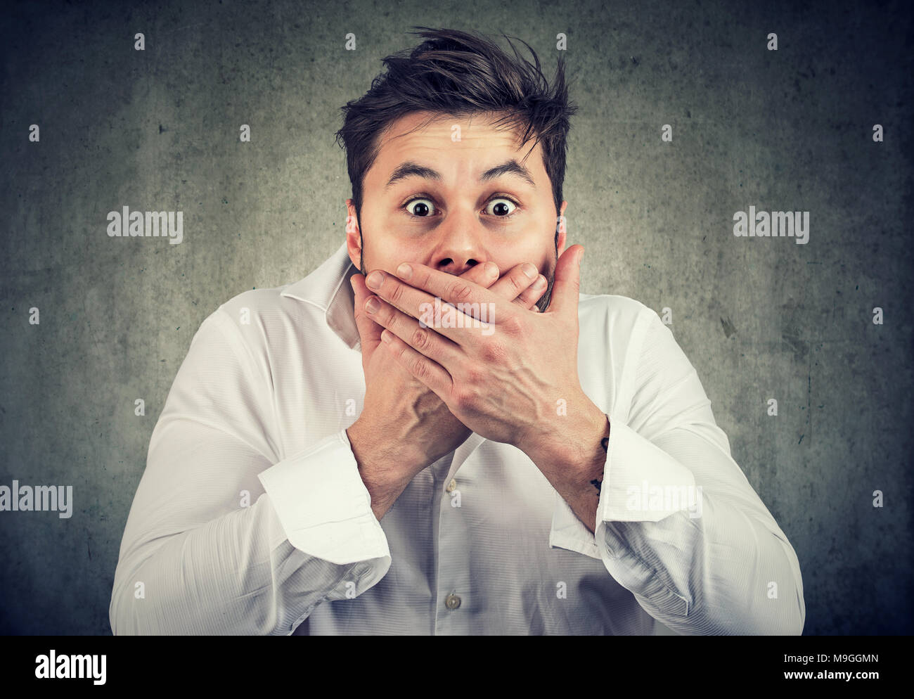 Young shocked man in white shirt covering mouth holding scream while looking at camera with amazed face expression. - Stock Image