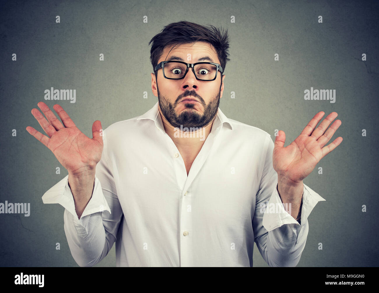 Young handsome man in eyeglasses looking super confused and shrugging with shoulders looking at camera. - Stock Image