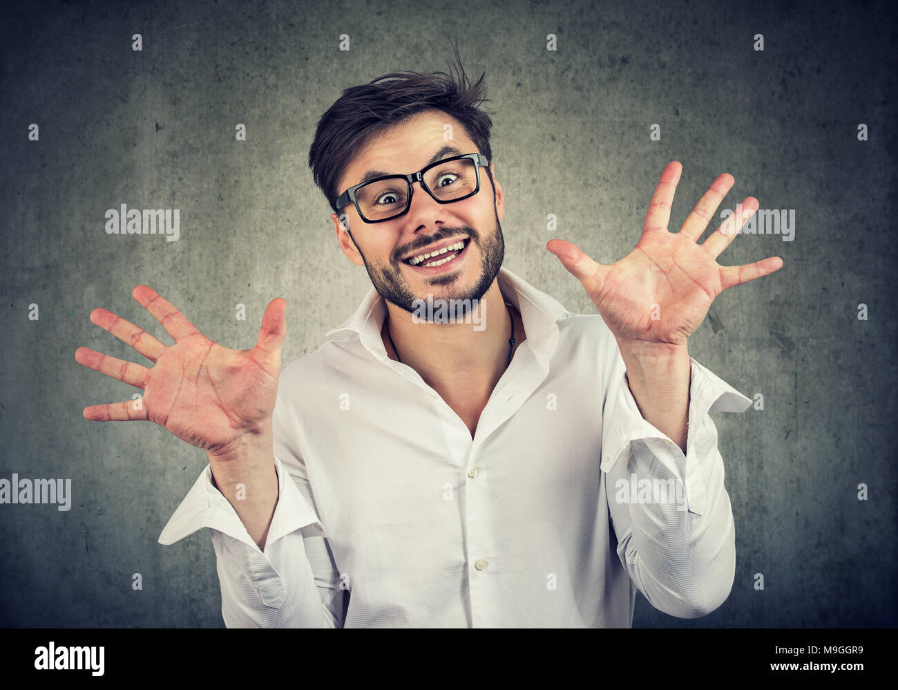 Young excited man making faces and gesturing in surprise looking at camera. - Stock Image
