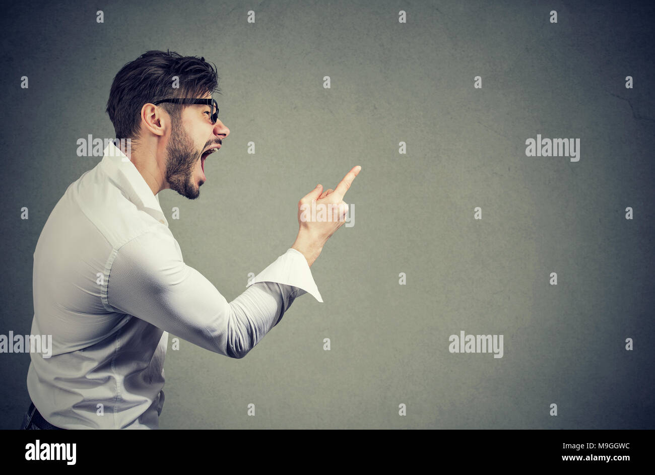 Side view of man threatening with finger while shouting loudly and looking away. - Stock Image