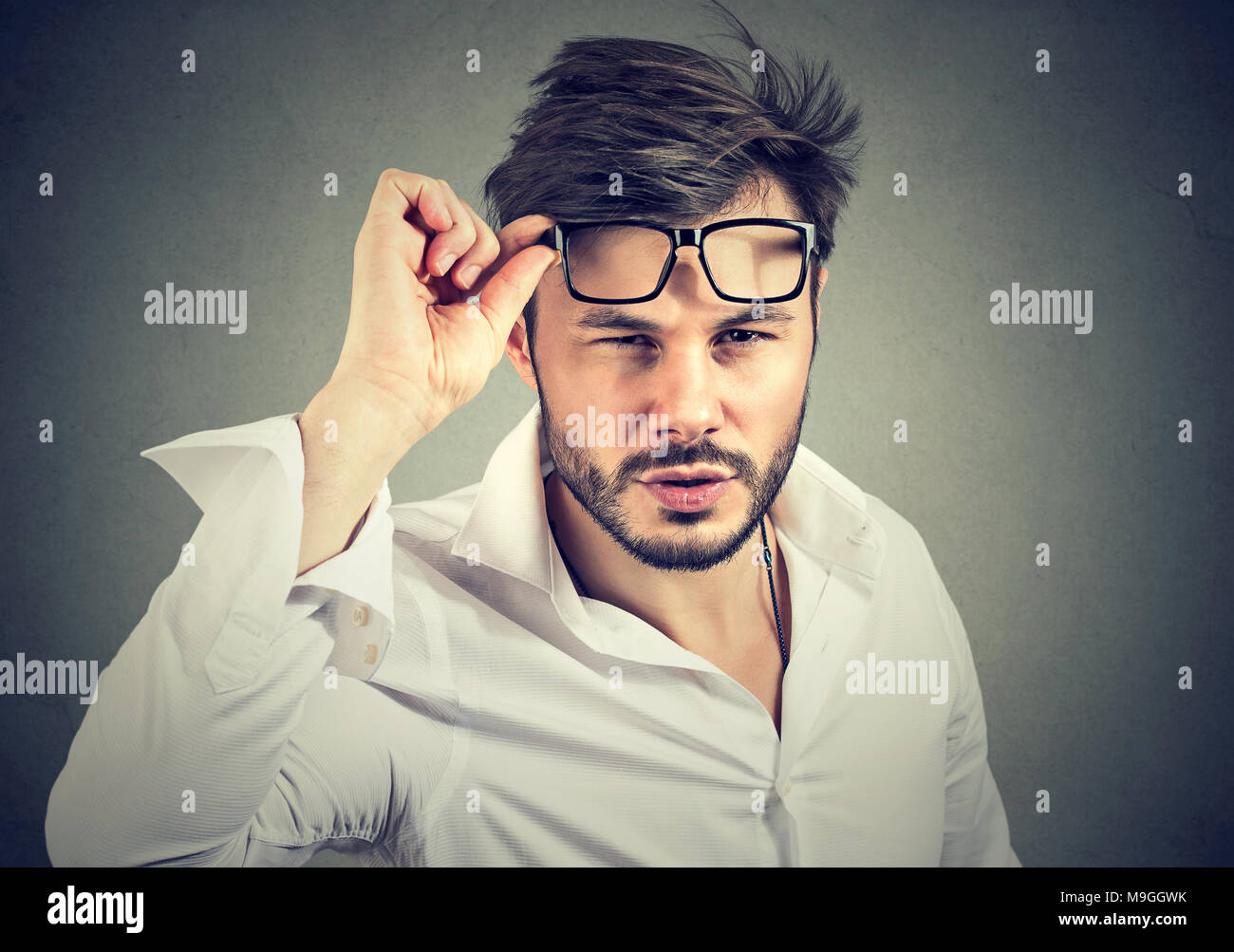 Young man in formal shirt taking off eyeglasses looking at camera with doubts. Stock Photo