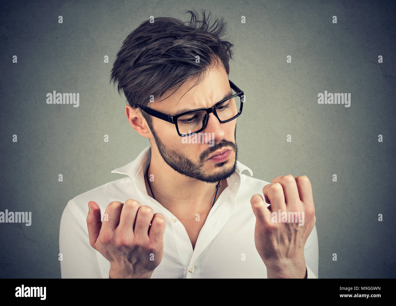 Young serious man with obsessive compulsive disorder exploring cleanliness of hands. - Stock Image