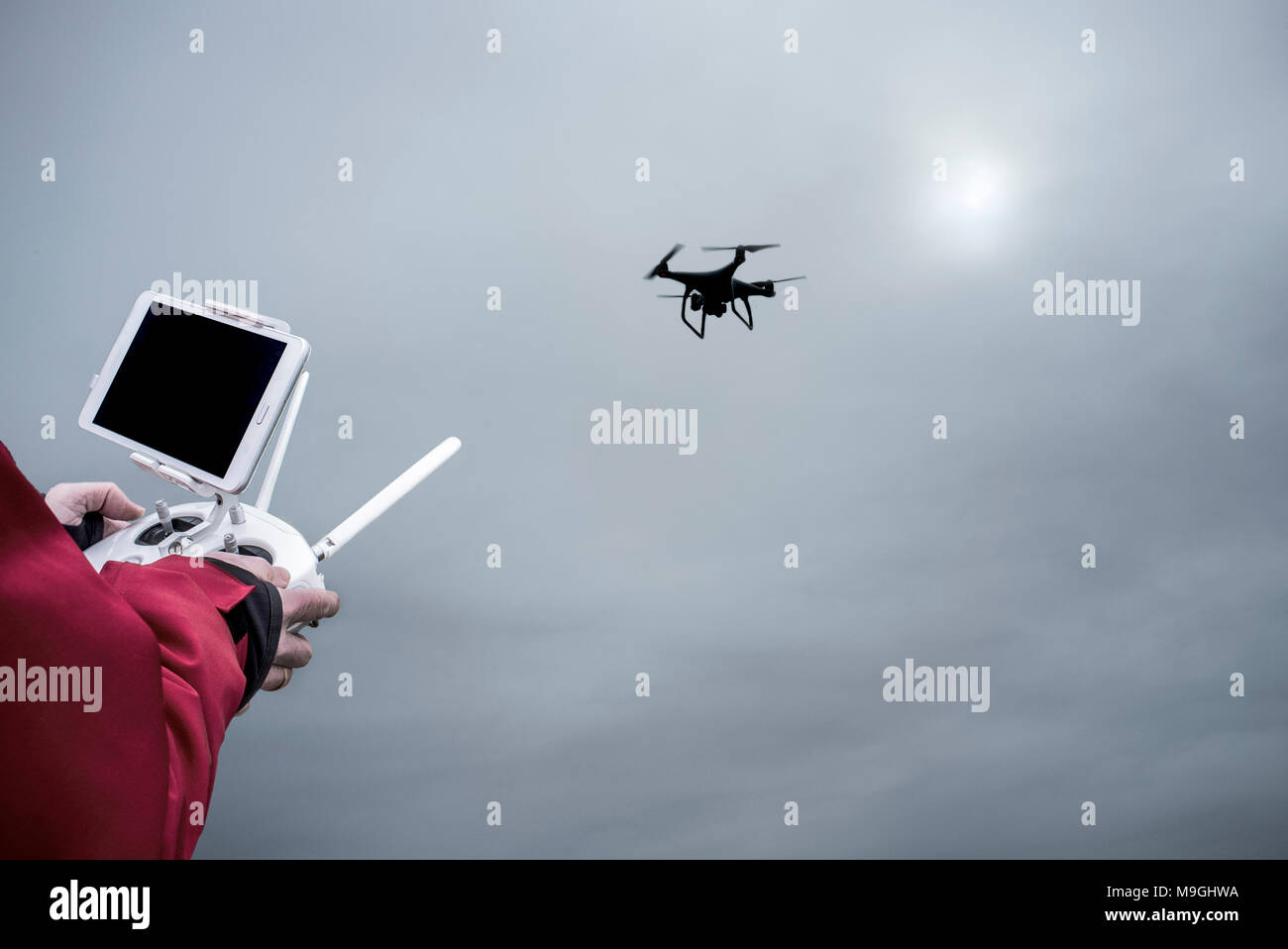 Pilot flying drone with FPV or First Person View device on remote controller. Approaching maneuver - Stock Image