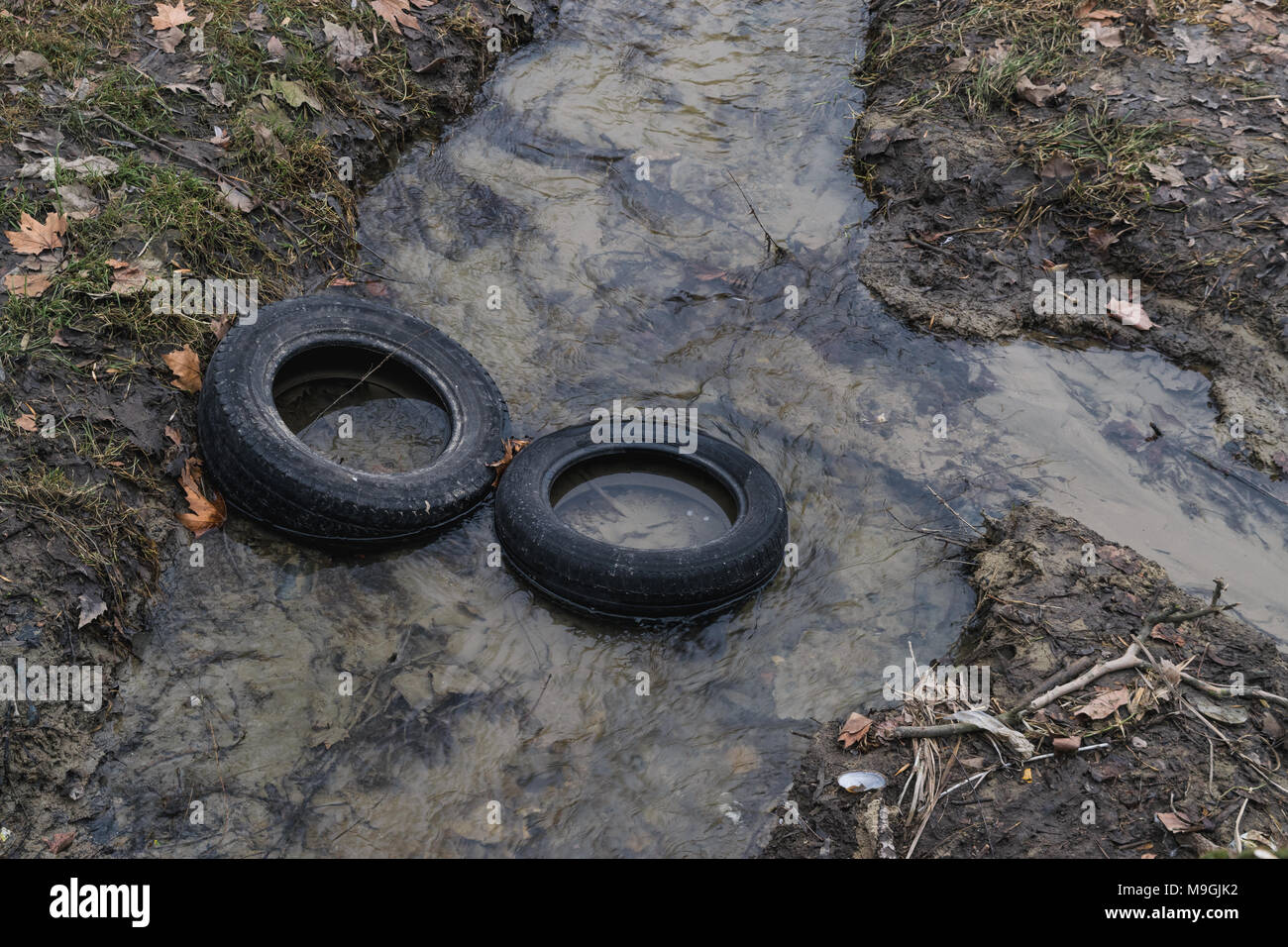 Two tires in a river, pollution concept. - Stock Image
