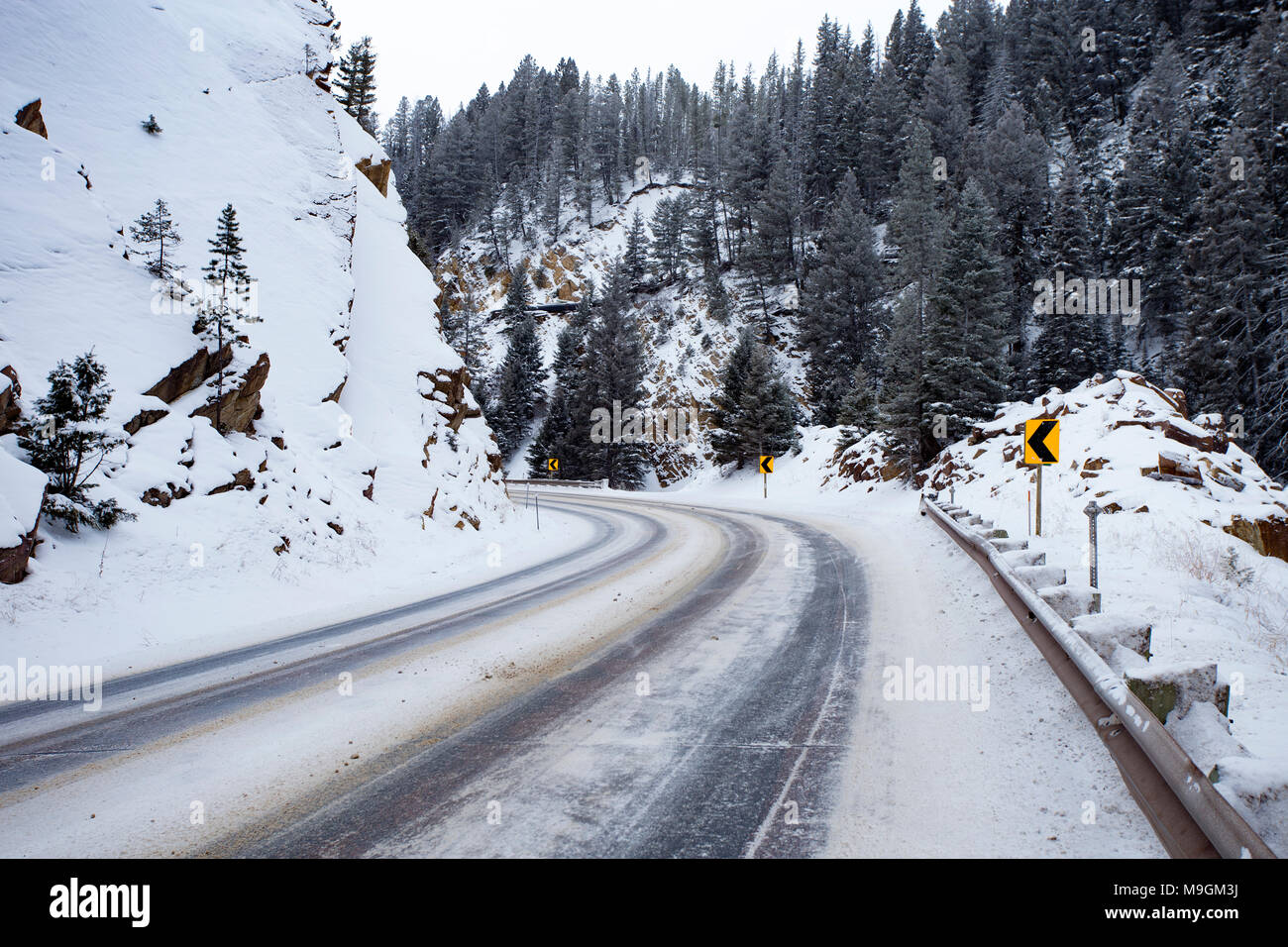 Icy road conditions coming up on a sharp curve, at Georgetown Pass, on Montana Highway 1, southeast of Philipsburg, MT. - Stock Image
