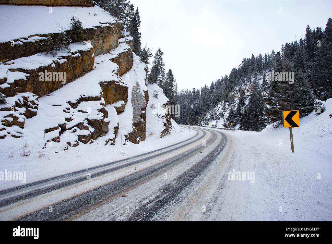 A sharp bend in the road with icy road conditions, at Georgetown Pass, on Montana Highway 1, southeast of Philipsburg, MT. - Stock Image