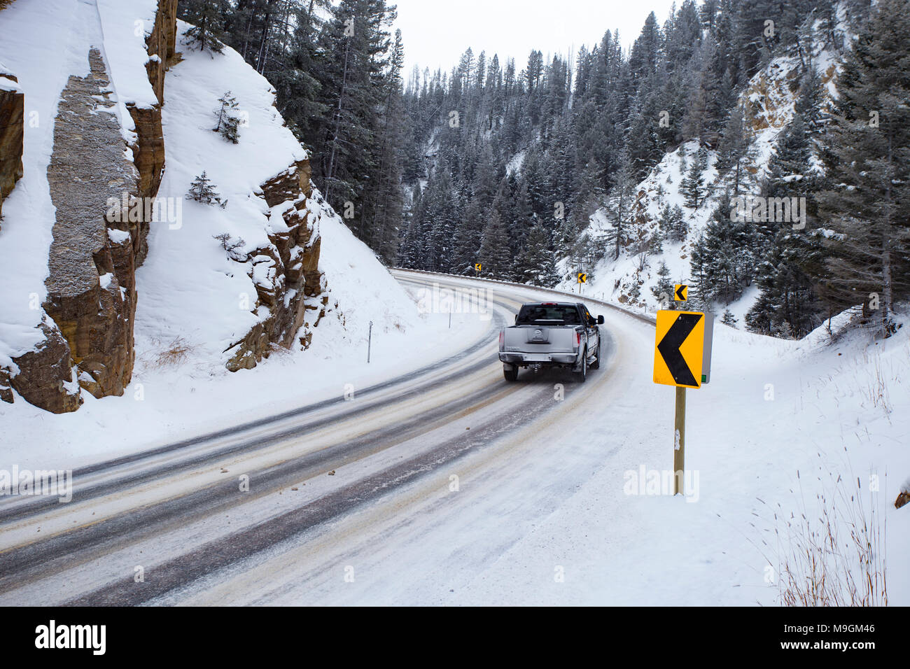 A Nissan Titan truck navigating an icy bend at Georgetown Pass, on Montana Highway 1, southeast of Philipsburg, MT. - Stock Image
