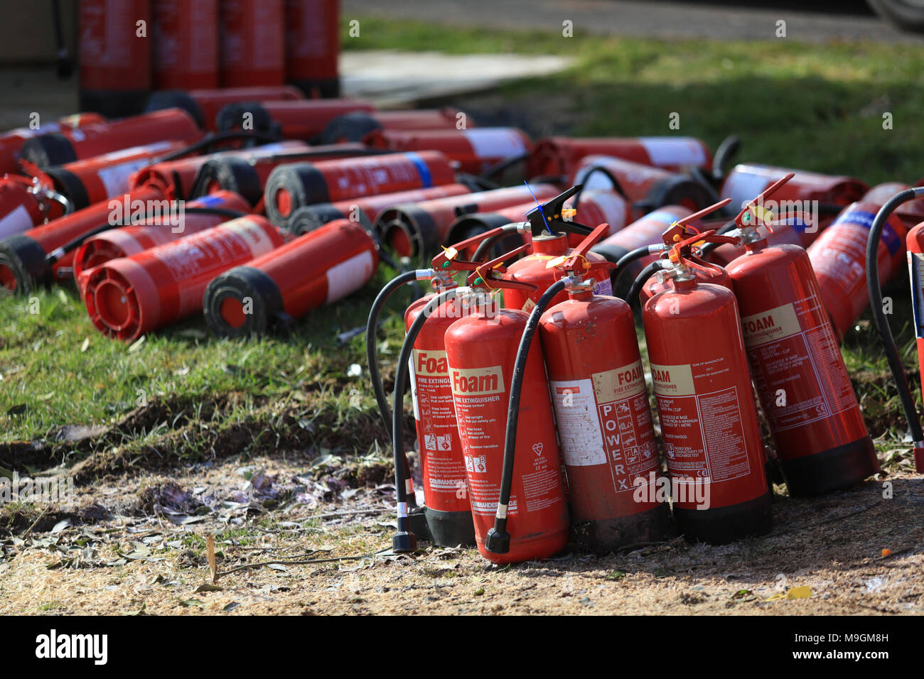 Fire extinguishers being used by motor sport marshals for fire fighting training. - Stock Image