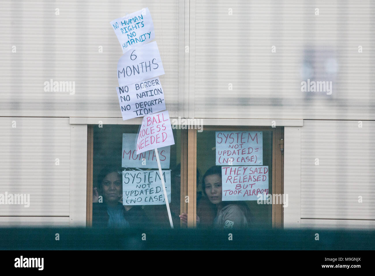 Milton Ernest, UK. 24th March, 2018. Detainees inside Yarl's Wood Immigration Removal Centre wave to and hold messages for hundreds of anti-detention  - Stock Image