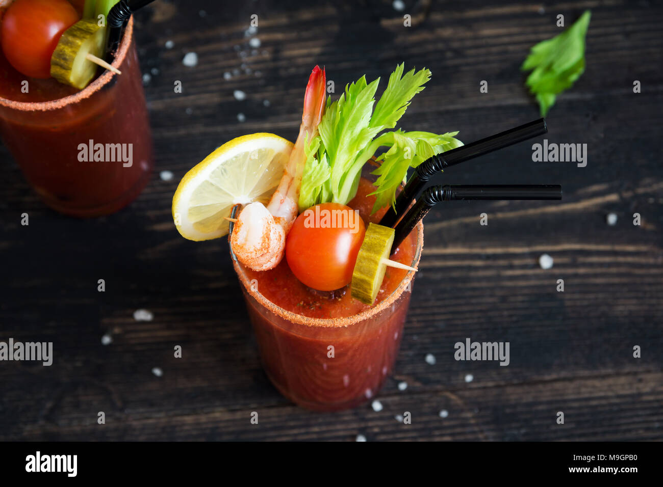 Bloody Mary Cocktail in glass with garnishes. Tomato Bloody Mary spicy drink on black background with copy space. - Stock Image