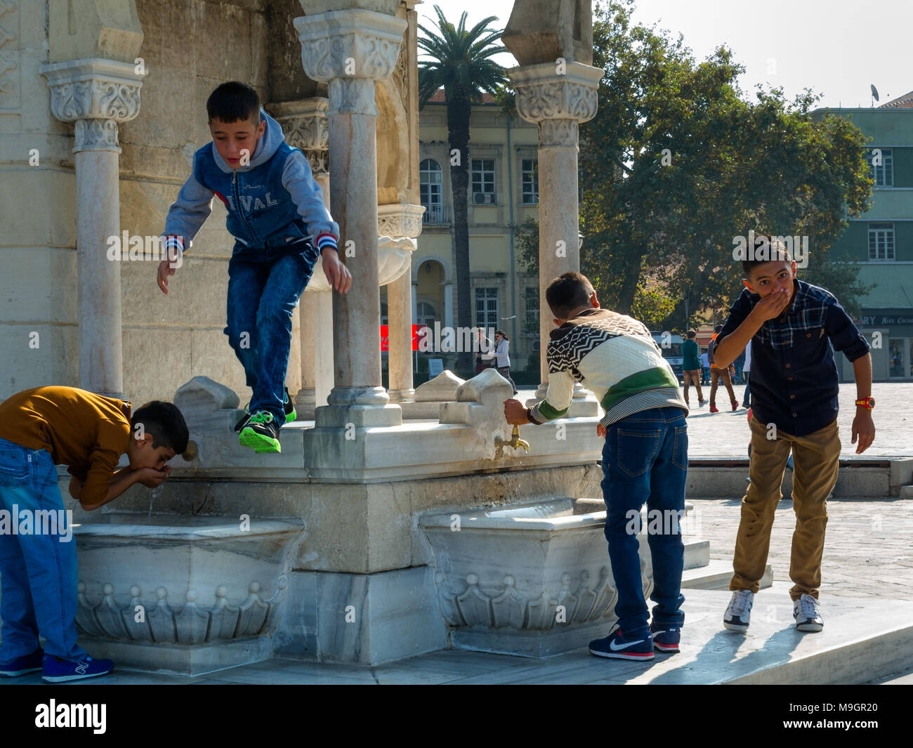 IZMIR, TURKEY - OCTOBER 04, 2014:  Young generation at the Clock Tower, Ottoman architecture of historic symbol of Izmir at the  Konak Square, built i Stock Photo