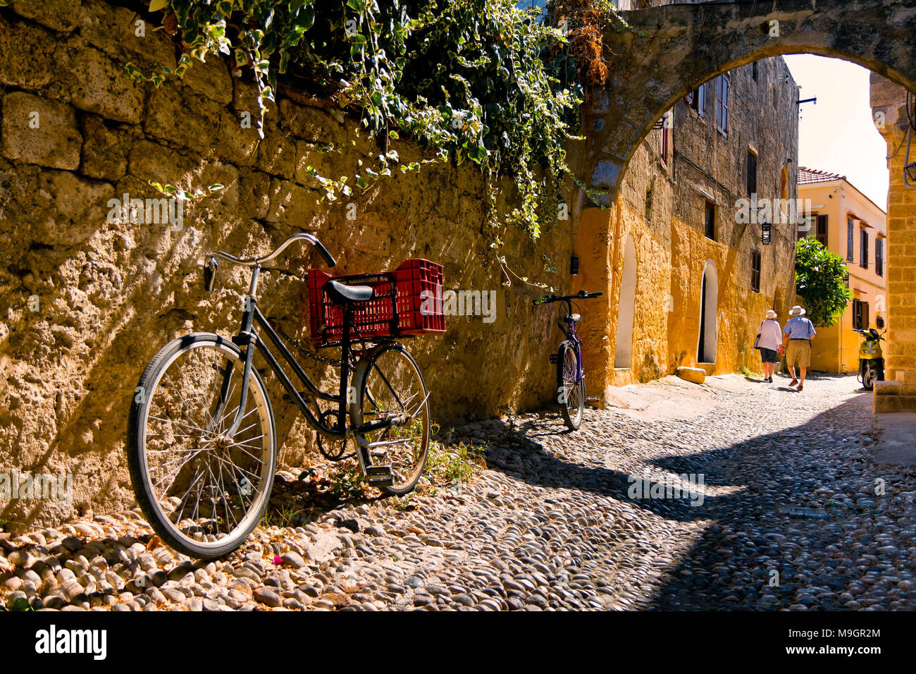 RHODES, GREECE - SEPTEMBER 30: Tourists admire charming secret narrow streets of Rhodes Island, bicycles in the foreground. September 30 2011, Greece - Stock Image