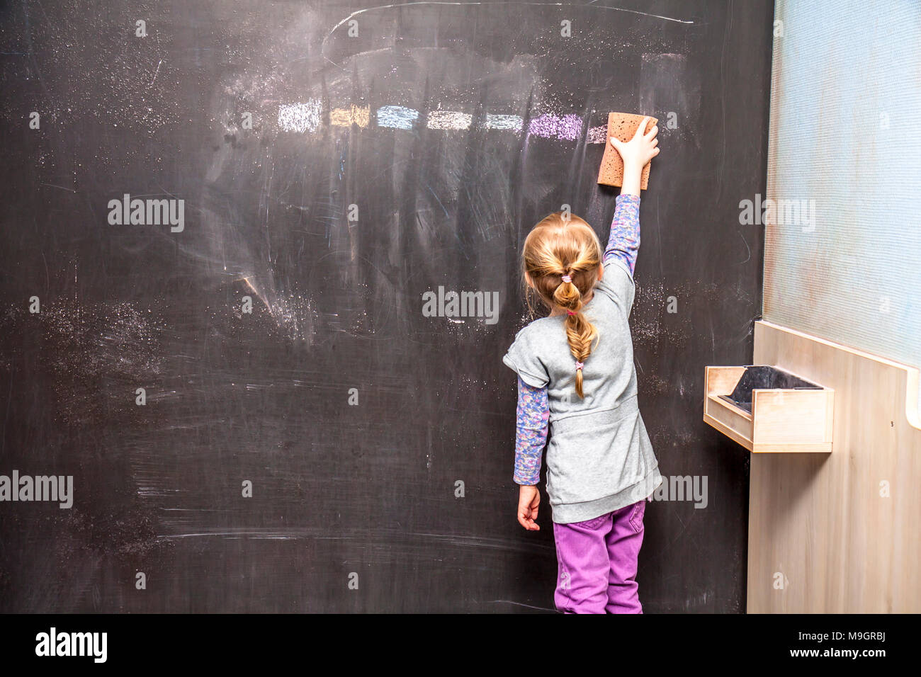 Back view of a little girl cleaning chalkboard. - Stock Image