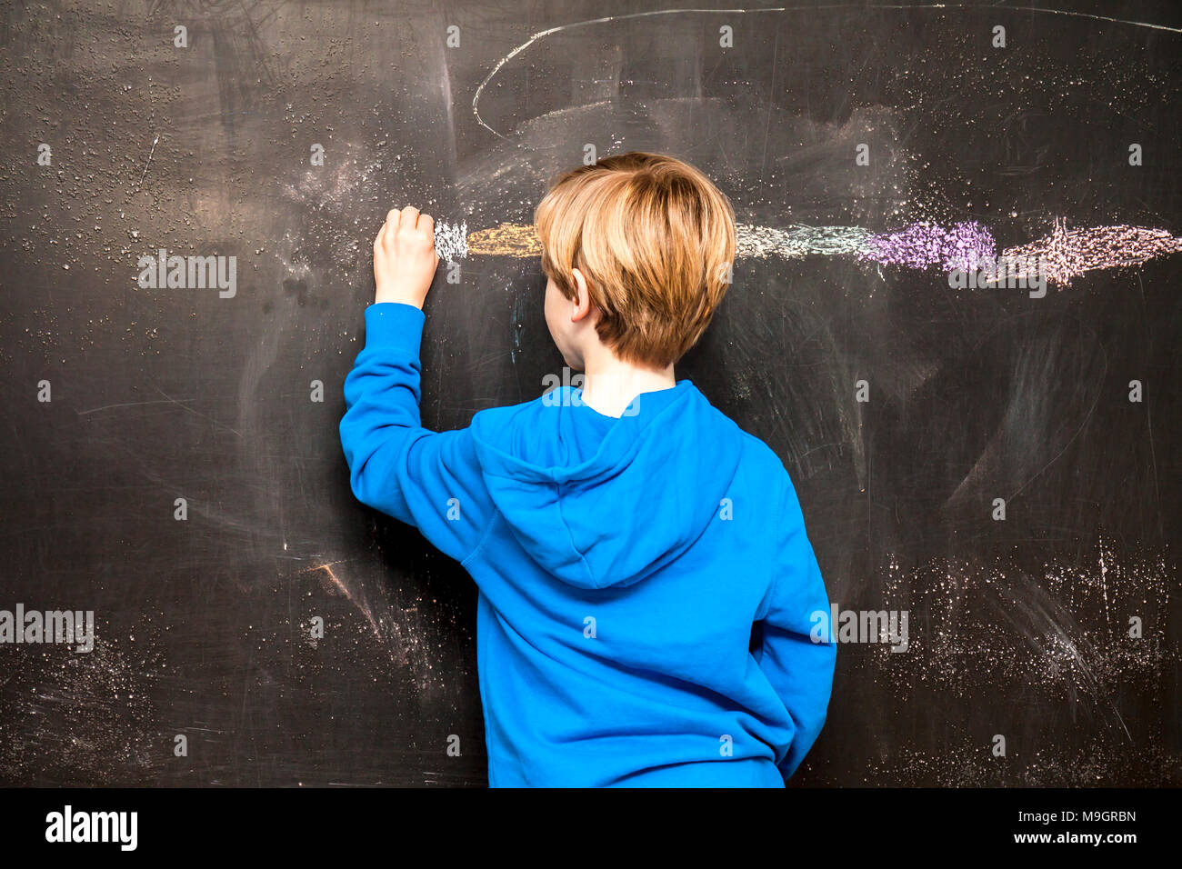 Back view of a little boy painting something on a chalkboard. - Stock Image