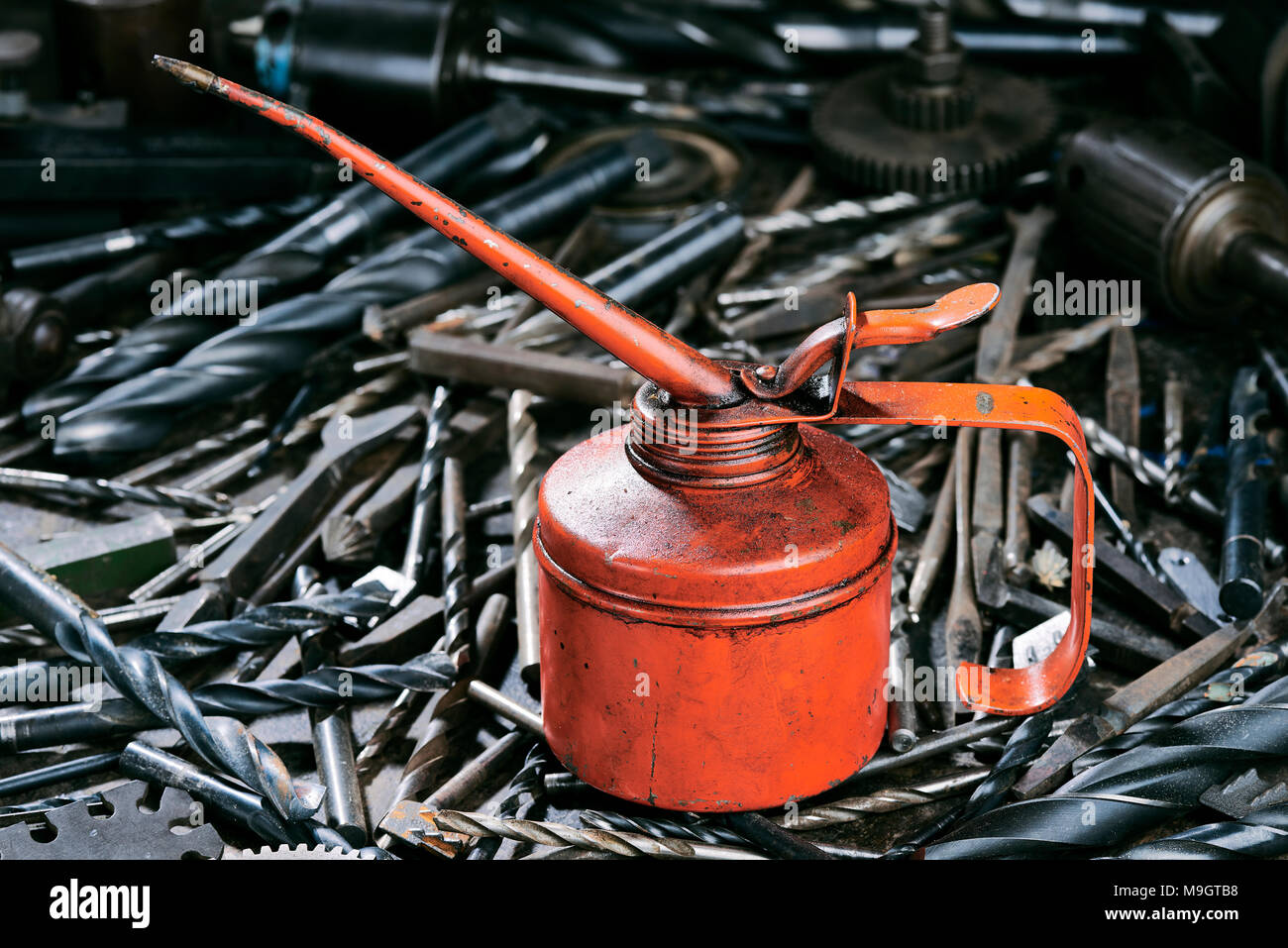 Orange oil can on drill bits - Stock Image