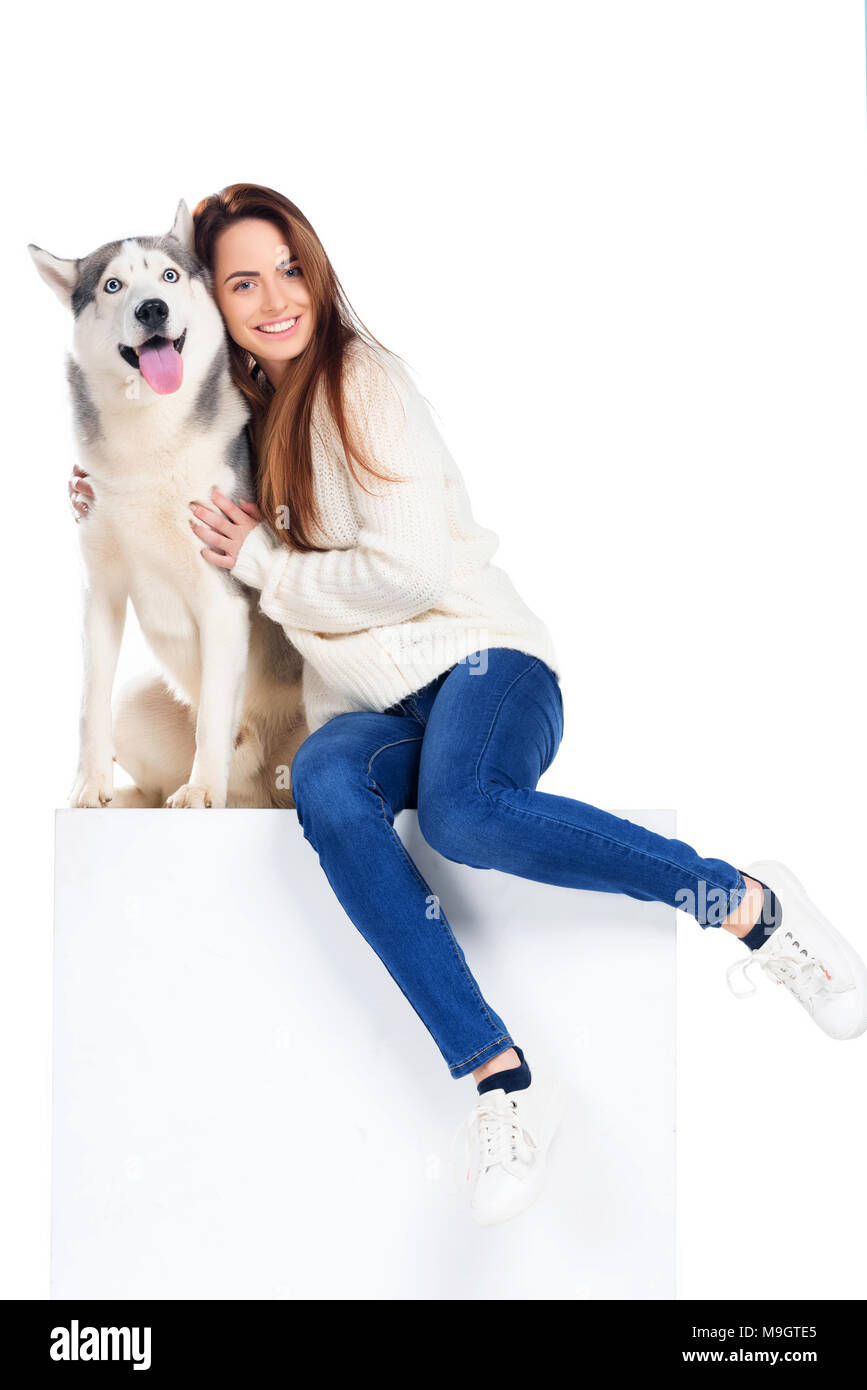 husky dog and woman in knitted hat and scarf sitting on white cube, isolated on white - Stock Image