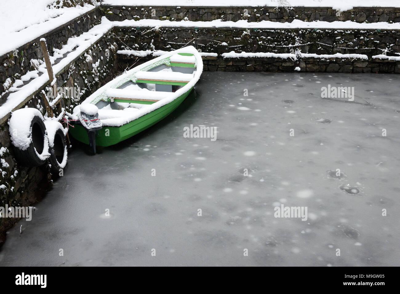 Green fishing boat moored in frozen water  Snowy Killarney