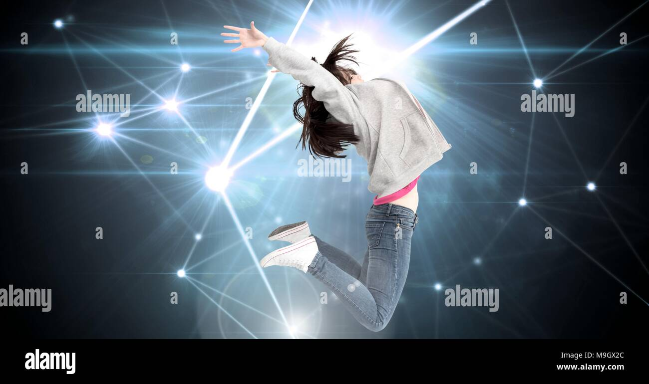 Woman jumping expressively with glowing star spangled connections - Stock Image