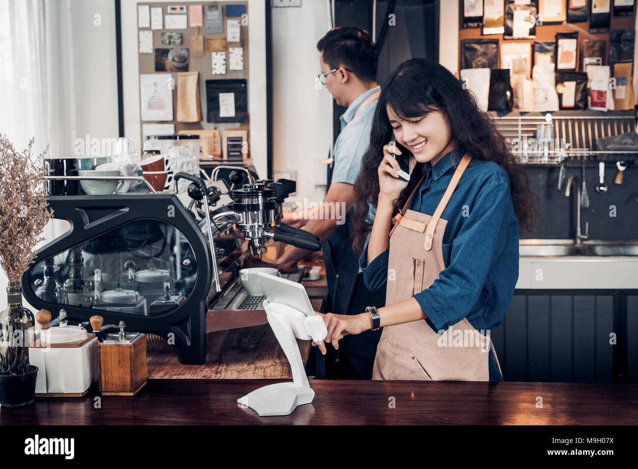 Asia Barista waiter use tablet take order from customer in coffee shop,cafe owner writing drink order at counter bar,Food and drink business concept,S - Stock Image