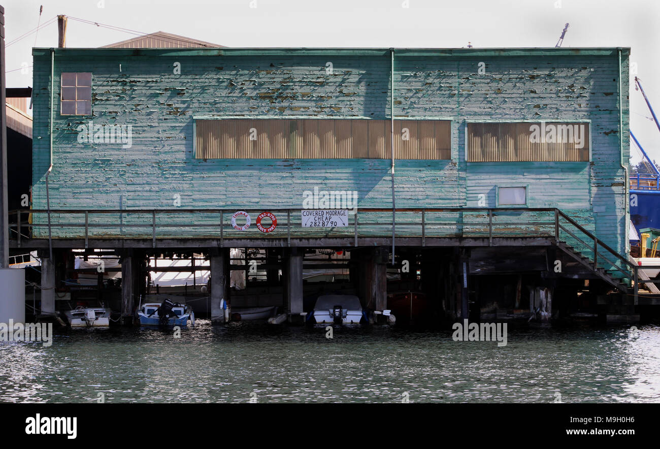Green building with cracking and peeling paint. Covered moorage underneath. Fisherman's Terminal, Seattle - Stock Image