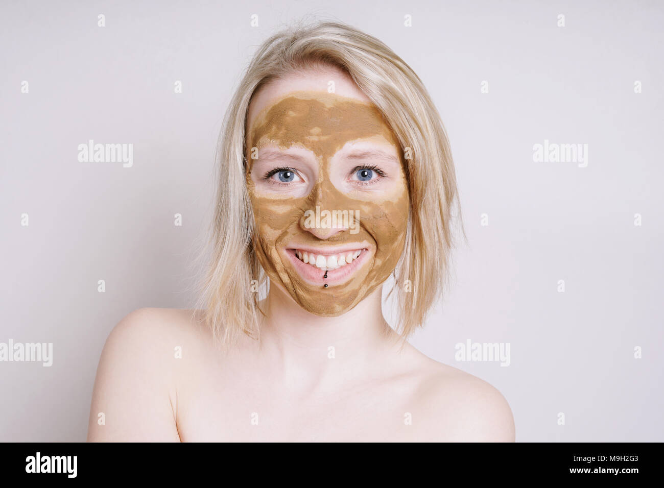 young woman with healing earth or clay beauty facial mask - Stock Image