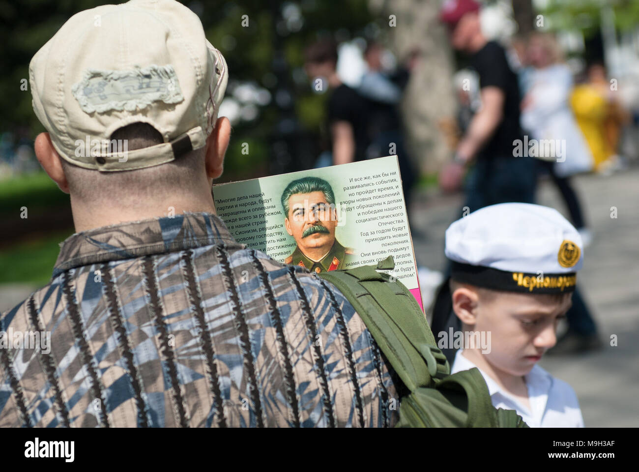 36fa6e07867 adult man holding a portrait of comrade Stalin near boy wearing sailor cap  on russian Victory
