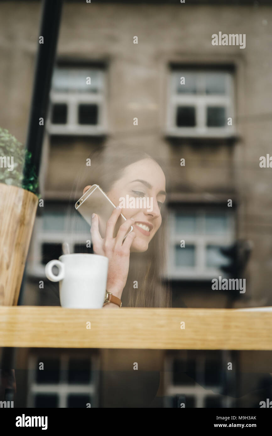 beautiful young woman talking on the phone in cafe. bright sunny morning in cafe bar, shot through the window, with city reflections - Stock Image