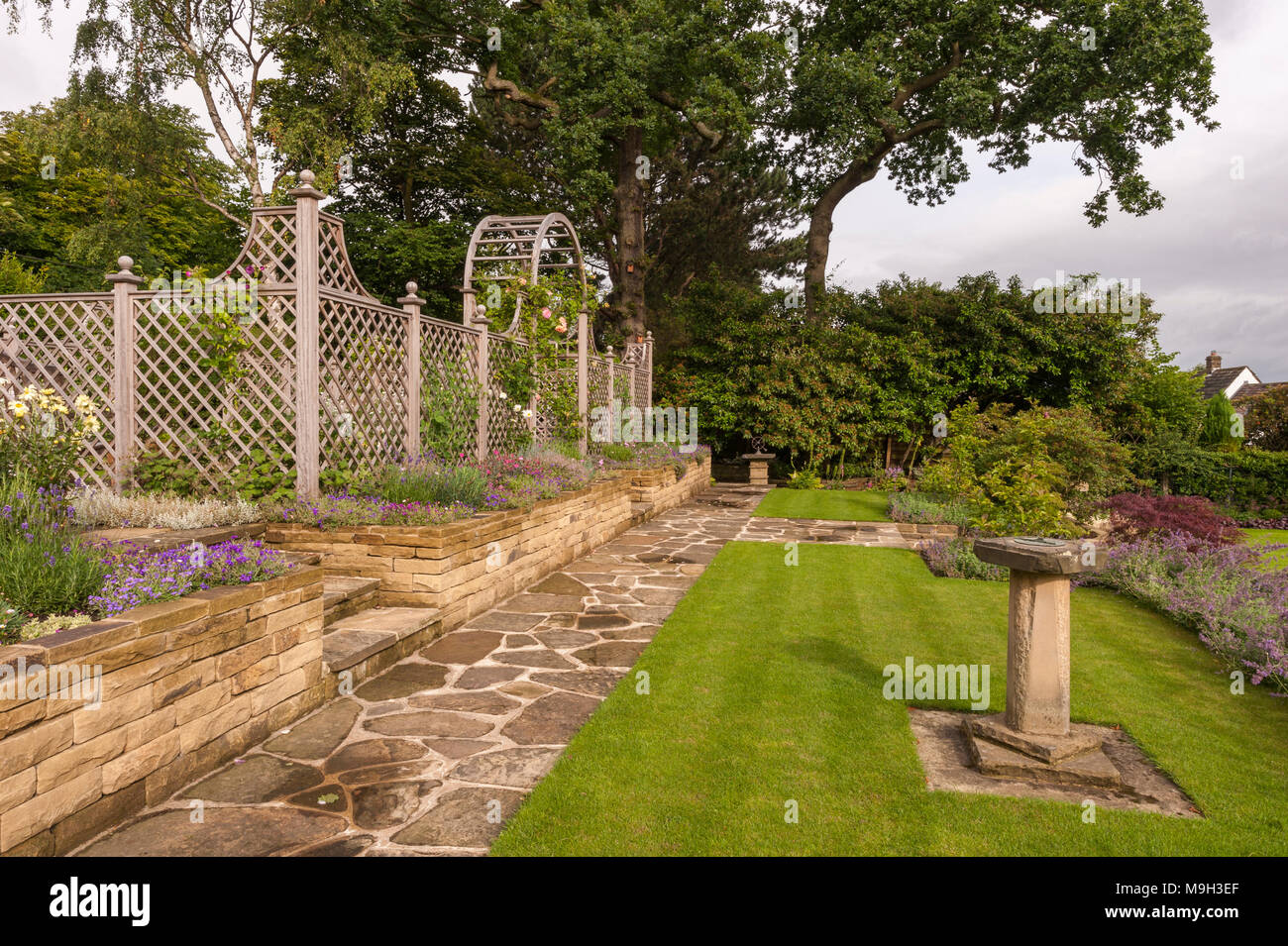 Path, flowering plants on border, lawn, stone wall, wooden trellis arch & screen - beautiful, designed, landscaped, garden - West Yorkshire, England. Stock Photo