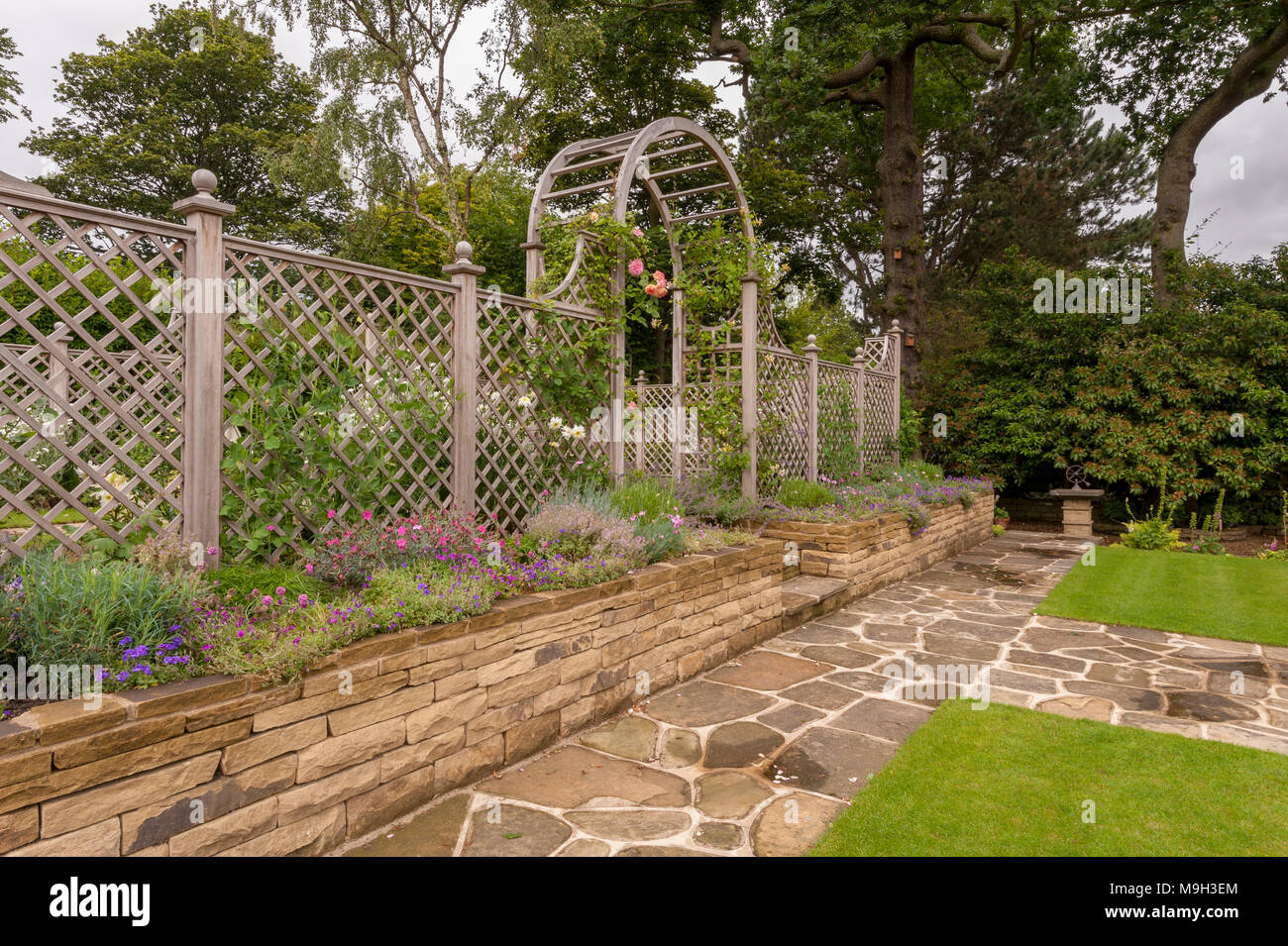 Path, flowering plants on border, lawn, stone wall, wooden trellis ...