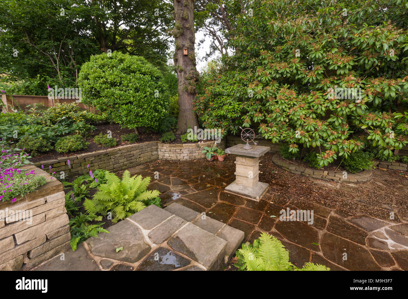 Small shady paved terraced area with stone sundial, raised ... on stone walkways ideas, stone fireplaces ideas, stone fencing ideas, stone fire pits ideas, stone paths ideas, stone shed ideas, stone mulch ideas,