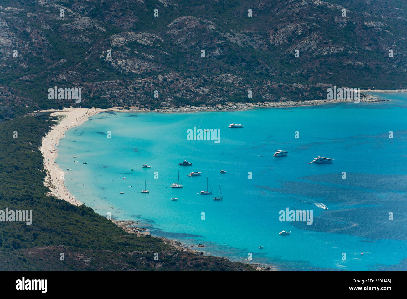 Aerial image of Corsica turquoise coastlinge showing Pointe de Curza and Punta di Furmiguli and Plage de Saleccia with private yachts Stock Photo