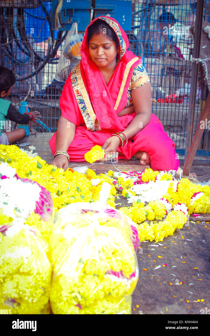 A female florist preparing garlands in a local street market of New Delhi, India. September 29, 2017. - Stock Image