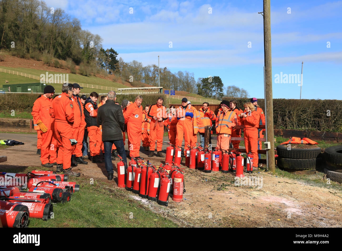 Motor sport marshals being instructed in the use of fire fighting equipment. - Stock Image